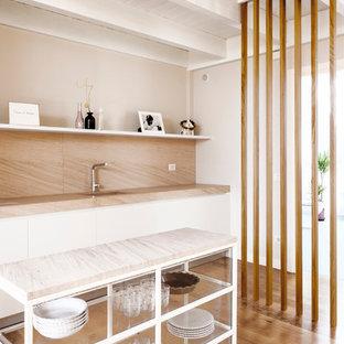 Immagine di una cucina lineare minimal con ante lisce, ante bianche, paraspruzzi in lastra di pietra, isola, lavello sottopiano, paraspruzzi beige, pavimento in legno massello medio e top beige