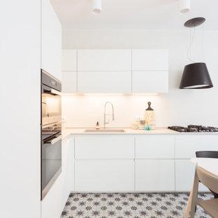 Foto di una grande cucina a L scandinava chiusa con top in superficie solida, paraspruzzi bianco, pavimento multicolore, lavello sottopiano, ante lisce, ante bianche e elettrodomestici in acciaio inossidabile