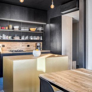 Idee per una cucina design di medie dimensioni con lavello a vasca singola, ante lisce, ante nere, top in legno, paraspruzzi in legno, pavimento in cemento, isola, pavimento grigio, paraspruzzi beige, elettrodomestici da incasso e top beige