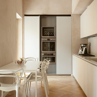 Photo of a mid-sized modern single-wall separate kitchen in Turin with flat-panel cabinets, no island, an integrated sink, beige cabinets, beige splashback, stainless steel appliances, light hardwood floors, beige floor and beige benchtop.