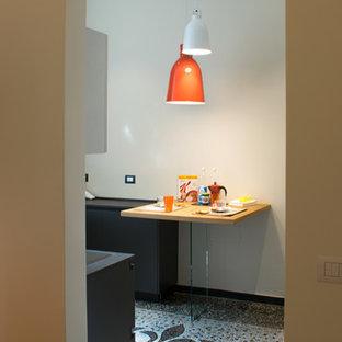 Ejemplo de cocina en U, bohemia, pequeña, cerrada, sin isla, con fregadero encastrado, armarios con paneles lisos, puertas de armario grises, encimera de laminado, electrodomésticos con paneles y suelo de terrazo