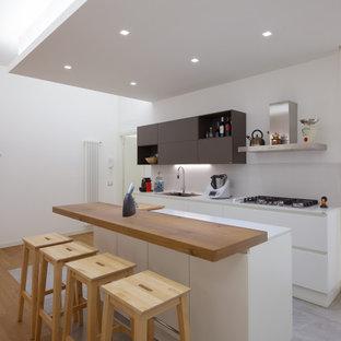 Ispirazione per una cucina parallela contemporanea con lavello sottopiano, ante lisce, ante bianche, isola, pavimento grigio e top bianco
