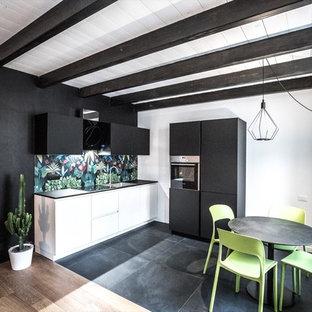 他の地域の小さいインダストリアルスタイルのおしゃれなキッチン (ドロップインシンク、フラットパネル扉のキャビネット、白いキャビネット、ラミネートカウンター、マルチカラーのキッチンパネル、セラミックタイルのキッチンパネル、シルバーの調理設備、セラミックタイルの床、黒い床、黒いキッチンカウンター) の写真