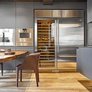 Ispirazione per una cucina minimal con ante lisce, ante grigie, paraspruzzi grigio, elettrodomestici in acciaio inossidabile e parquet chiaro
