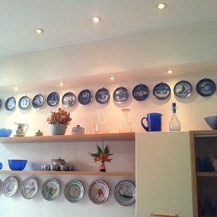 他の地域の広いコンテンポラリースタイルのおしゃれなII型キッチン (ダブルシンク、ステンレスカウンター、テラゾーの床、赤い床) の写真