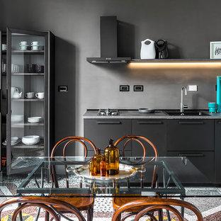 フィレンツェの中サイズのモダンスタイルのおしゃれなキッチン (黒いキャビネット、コンクリートカウンター、アイランドなし、マルチカラーの床、フラットパネル扉のキャビネット、シングルシンク、グレーのキッチンカウンター) の写真