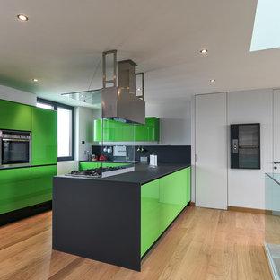 Foto di una cucina contemporanea con ante lisce, ante verdi, top in superficie solida, paraspruzzi con lastra di vetro, elettrodomestici in acciaio inossidabile, parquet chiaro e isola