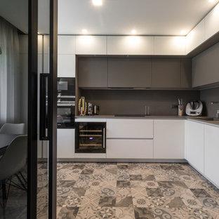 他の地域の広いモダンスタイルのおしゃれなキッチン (ドロップインシンク、フラットパネル扉のキャビネット、白いキャビネット、タイルカウンター、グレーのキッチンパネル、磁器タイルのキッチンパネル、シルバーの調理設備、セラミックタイルの床、アイランドなし、茶色い床、グレーのキッチンカウンター) の写真