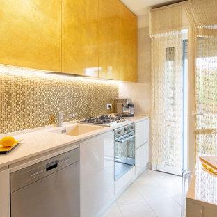 Immagine di una cucina parallela design chiusa e di medie dimensioni con lavello integrato, ante lisce, ante bianche, paraspruzzi giallo, elettrodomestici in acciaio inossidabile, nessuna isola, pavimento bianco e top beige