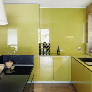 Immagine di una cucina a L minimal di medie dimensioni con ante lisce, isola, lavello da incasso e parquet chiaro