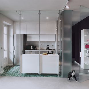 This is an example of a mid-sized contemporary galley separate kitchen in Turin with a single-bowl sink, flat-panel cabinets, white cabinets, laminate benchtops, white splashback, porcelain splashback, stainless steel appliances, cement tiles, with island and green floor.