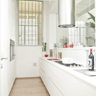 Foto di una cucina a corridoio minimal chiusa con ante lisce, ante bianche, paraspruzzi bianco e parquet chiaro
