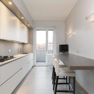 Immagine di una cucina lineare contemporanea chiusa con ante lisce, ante bianche, lavello sottopiano, paraspruzzi grigio, pavimento grigio e top grigio
