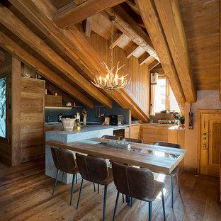Immagine di una cucina abitabile stile rurale con pavimento in legno massello medio e penisola