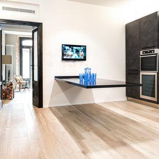 Foto di una cucina lineare minimal con ante nere, paraspruzzi nero, elettrodomestici in acciaio inossidabile, top nero, ante lisce, parquet chiaro, pavimento beige e nessuna isola