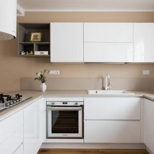 Foto di una cucina ad U design con lavello da incasso, ante lisce, ante bianche, elettrodomestici bianchi, pavimento in legno massello medio, penisola, pavimento marrone e top beige