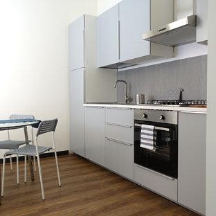Idee per una cucina lineare design chiusa e di medie dimensioni con lavello da incasso, ante lisce, ante grigie, top in laminato, paraspruzzi grigio, paraspruzzi in gres porcellanato, pavimento in laminato, nessuna isola, top grigio, elettrodomestici da incasso e pavimento marrone