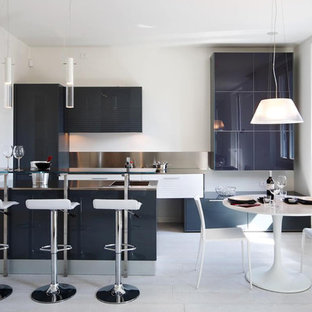 This is an example of a contemporary galley eat-in kitchen in Milan with an integrated sink, flat-panel cabinets, blue cabinets, stainless steel benchtops, metallic splashback, panelled appliances and a peninsula.