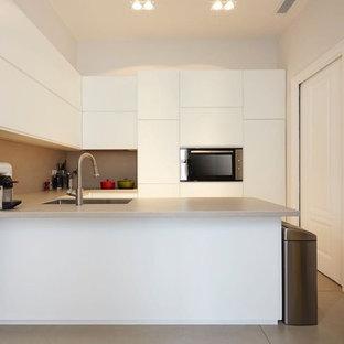 Esempio di una cucina ad U minimalista con ante lisce, ante bianche, lavello a vasca singola, paraspruzzi grigio, elettrodomestici da incasso, penisola, pavimento grigio e top grigio