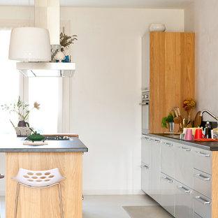 Diseño de cocina de galera, nórdica, con armarios con paneles lisos, puertas de armario en acero inoxidable, una isla y suelo de baldosas de porcelana