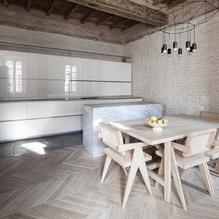 Foto di una cucina abitabile minimal con parquet chiaro, ante lisce, ante bianche e penisola