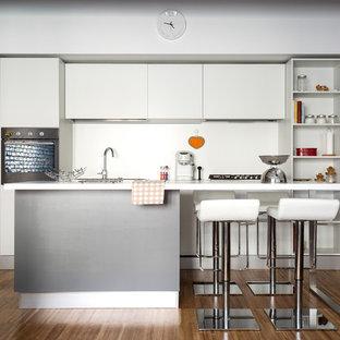 Immagine di una cucina lineare moderna di medie dimensioni con ante lisce, ante bianche, paraspruzzi bianco, pavimento in legno massello medio, un'isola, pavimento marrone e lavello sottopiano
