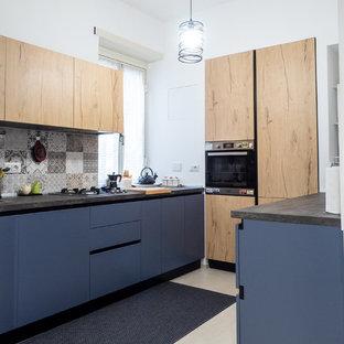 Foto di una cucina design con ante lisce, ante blu, paraspruzzi multicolore, elettrodomestici neri, pavimento beige e top grigio