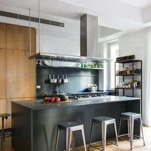 Immagine di una cucina parallela industriale con ante lisce, ante marroni, paraspruzzi grigio, pavimento in legno massello medio, isola, pavimento marrone e top grigio