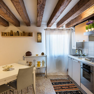 This is an example of a small country single-wall eat-in kitchen in Venice with flat-panel cabinets, white cabinets, white splashback, no island, a drop-in sink, stainless steel appliances and multi-coloured floor.