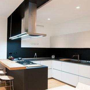 Modelo de cocina en U, contemporánea, pequeña, cerrada, con encimera de vidrio, salpicadero negro, suelo de madera clara, península, fregadero de doble seno, armarios con paneles lisos y puertas de armario grises