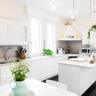 Esempio di una grande cucina classica con lavello sottopiano, ante con bugna sagomata, ante bianche, top in granito, paraspruzzi in gres porcellanato, elettrodomestici in acciaio inossidabile, parquet scuro, pavimento marrone, paraspruzzi grigio e top grigio
