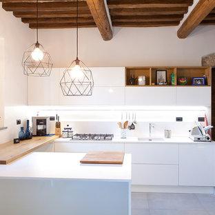 Foto di una cucina ad U mediterranea di medie dimensioni con ante lisce, ante bianche, paraspruzzi bianco, penisola, pavimento grigio, lavello integrato, elettrodomestici da incasso e pavimento in cemento