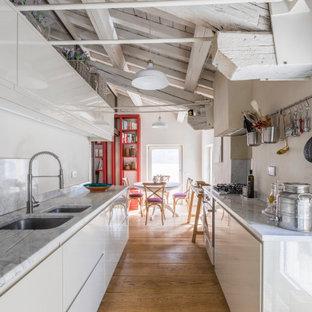 Immagine di una cucina mediterranea di medie dimensioni con lavello a doppia vasca, ante lisce, ante bianche e top in marmo
