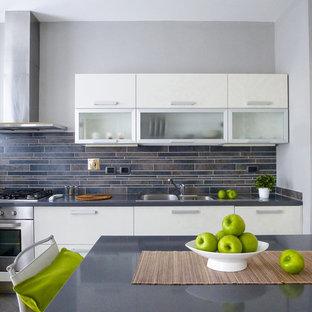 Foto di una piccola cucina design con lavello a doppia vasca, ante lisce, ante in acciaio inossidabile, paraspruzzi nero, paraspruzzi con piastrelle a listelli, elettrodomestici in acciaio inossidabile e pavimento grigio