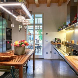 Idee per una cucina tradizionale di medie dimensioni con ante lisce, ante in acciaio inossidabile, top in acciaio inossidabile, elettrodomestici in acciaio inossidabile, pavimento in cemento, pavimento grigio, paraspruzzi bianco, nessuna isola e lavello da incasso