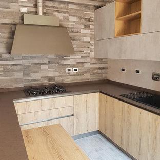 ボローニャの大きいモダンスタイルのおしゃれなキッチン (ドロップインシンク、フラットパネル扉のキャビネット、淡色木目調キャビネット、クオーツストーンカウンター、マルチカラーのキッチンパネル、ボーダータイルのキッチンパネル、シルバーの調理設備の、磁器タイルの床、グレーの床、茶色いキッチンカウンター) の写真