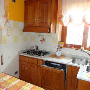 ローマの小さいカントリー風おしゃれなキッチン (ダブルシンク、インセット扉のキャビネット、中間色木目調キャビネット、大理石カウンター、黄色いキッチンパネル、セラミックタイルのキッチンパネル、パネルと同色の調理設備、セラミックタイルの床、アイランドなし) の写真