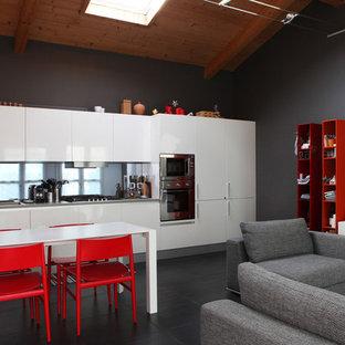 他の地域の中サイズのモダンスタイルのおしゃれなキッチン (ダブルシンク、フラットパネル扉のキャビネット、白いキャビネット、珪岩カウンター、グレーのキッチンパネル、ガラス板のキッチンパネル、シルバーの調理設備の、セラミックタイルの床、アイランドなし、黒い床、グレーのキッチンカウンター) の写真