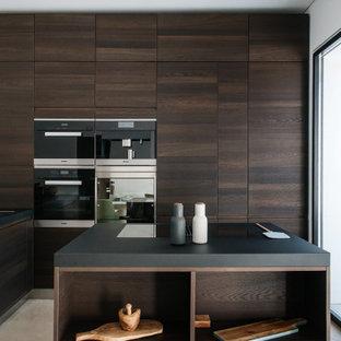 Foto di un cucina con isola centrale moderno con lavello a vasca singola, ante lisce, ante in legno bruno, elettrodomestici in acciaio inossidabile, pavimento grigio e top nero