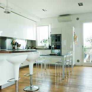 Ejemplo de cocina comedor en L, contemporánea, grande, con armarios con paneles lisos, puertas de armario blancas, salpicadero metalizado, electrodomésticos de acero inoxidable y suelo de madera clara