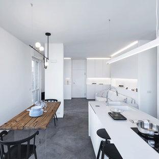 Ispirazione per una cucina minimal di medie dimensioni con lavello a doppia vasca, ante lisce, ante bianche, paraspruzzi bianco, elettrodomestici neri, isola, pavimento grigio e top bianco