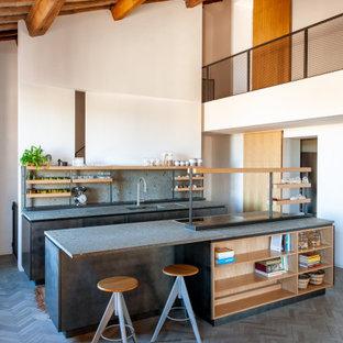 Idee per una grande cucina contemporanea con lavello integrato, ante lisce, ante grigie, paraspruzzi grigio, elettrodomestici da incasso, isola, pavimento grigio, top grigio, top in pietra calcarea, paraspruzzi in lastra di pietra e pavimento in mattoni