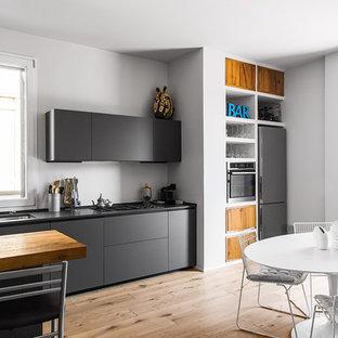 Ispirazione per una grande cucina abitabile nordica con ante lisce, elettrodomestici in acciaio inossidabile, parquet chiaro, lavello sottopiano, ante nere, pavimento beige e top nero