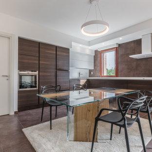 Foto di una cucina design con ante lisce, ante in legno bruno, paraspruzzi marrone, elettrodomestici in acciaio inossidabile, nessuna isola, pavimento marrone e top bianco