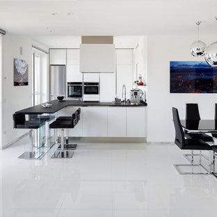 Immagine di una grande cucina abitabile contemporanea con pavimento in gres porcellanato, pavimento bianco, ante lisce, ante bianche, elettrodomestici in acciaio inossidabile, penisola e top nero
