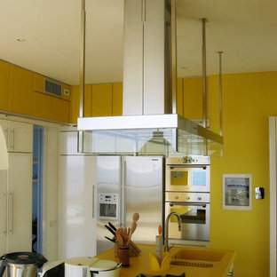 Photo of a large modern separate kitchen in Other with an integrated sink, flat-panel cabinets, white cabinets, solid surface benchtops, stainless steel appliances, ceramic floors, with island, yellow floor and yellow benchtop.