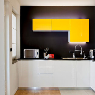 Exempel på ett avskilt, litet modernt l-kök, med en undermonterad diskho, släta luckor, gula skåp, bänkskiva i kvarts, svart stänkskydd, mellanmörkt trägolv och brunt golv