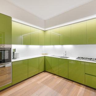 Immagine di una grande cucina a L design con ante lisce, ante verdi, paraspruzzi bianco e pavimento in legno massello medio