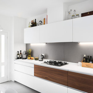 Design ideas for a mid-sized contemporary single-wall separate kitchen in Bologna with a single-bowl sink, flat-panel cabinets, white cabinets, solid surface benchtops, grey splashback, stainless steel appliances, porcelain floors, no island and grey floor.