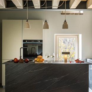 Ispirazione per una cucina parallela rustica di medie dimensioni con lavello da incasso, ante lisce, ante bianche, elettrodomestici neri, isola e top grigio